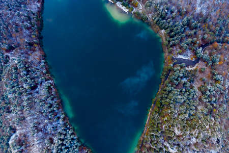 aerial view to blue lake Alatsee with snowy forest trees at winter
