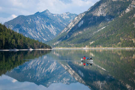 landscape of lake plansee with fishing boat and reflections of alp mountains