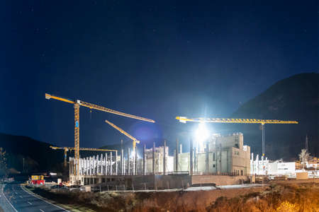 huge concrete construction site at night with four stationary tower cranes next highway