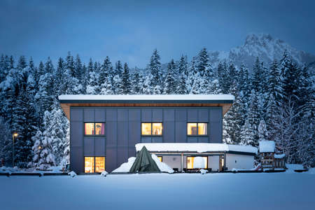 Frontal view of a single-family house with a solar thermal facade for sustainable and renewable heating and hot water energy at night in winter Stockfoto