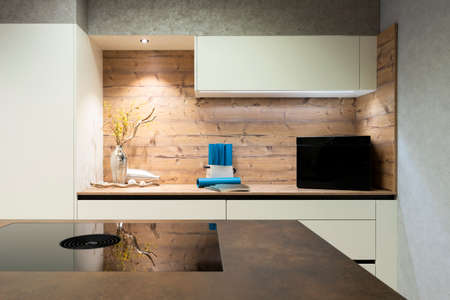 modern island stove, integrated extractor hood and wood look niche with decoration and wall unit