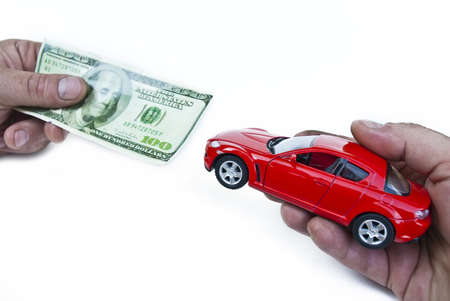 Car and money in hands on white photo