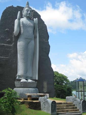 Giant Buddah standing on lotus in park Sri Lanka photo