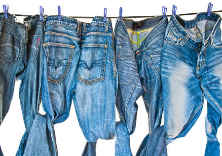 Some blue jeansdrying on washing line isolated on white photo