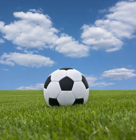 Soccer ball in green grass against a background of  cloudscape photo