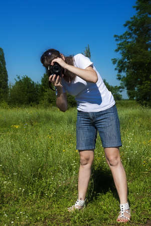 Young women is shoot landscape against a meadow and sky photo