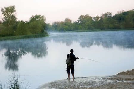 color image fish hook: The silhouette of fisherman in morning river