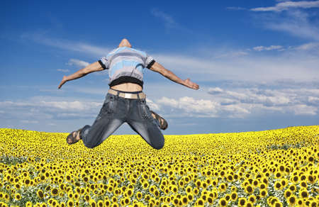 outdoor pursuit: Boy jumping against a background of field and sky Stock Photo
