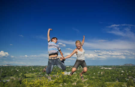 Boy and girl jumping against a background of beautiful sky photo