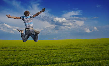 Boy jumping against a background of beautiful sky and meadow photo