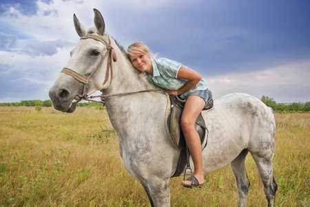 Young adult women ridind on gray horse on meadow, East Europe photo