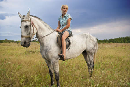 Young adult women ridind on gray horse on meadow, East Europe