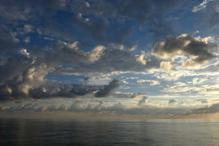 voluminous: Beautiful scenic clouds over the sea at sunset