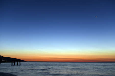 The last light of day creates dramatic colors in the sky over the sea. New moon rising.