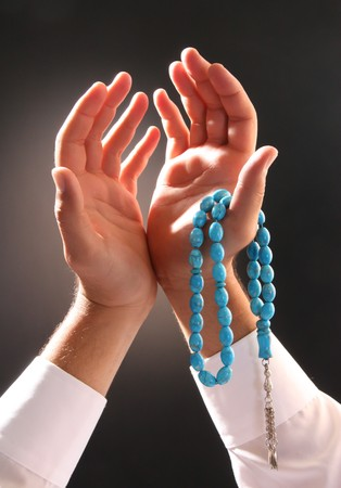 allah: mans hand holding a rosary in a pose of praying and asking