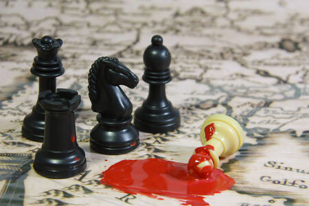 humanitarian aid: Chess stones on a map, 3 blacks against 1 white, with blood scene