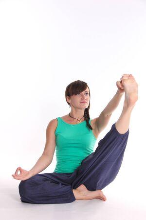 asanas: lady practicing yoga sitting and holding one toe on a white background