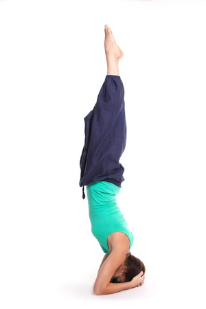 tight focus: girl practicing yoga with supported head stand position upside-down on a white background Stock Photo