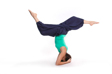 asanas: girl practicing yoga with supported head stand position upside-down on a white background Stock Photo