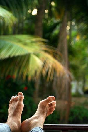 Mens feet on the porch of ship sailing through Kerala backwaters photo