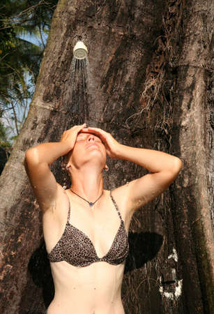 girl taking a shower under the tree photo