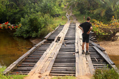 wood pillars: Man assessing the damage in the old wooden bridge Stock Photo