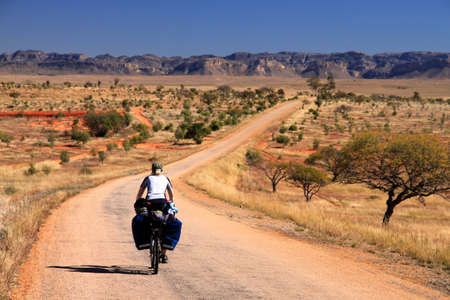 solo: Woman cycling  towards Parc National Isalo in Madagascar