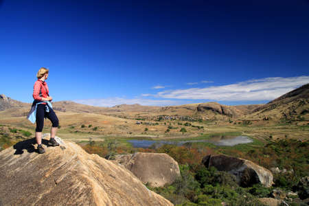 anja: Woman admiring the view from the rocky edge in Anja Reserve in Madagascar