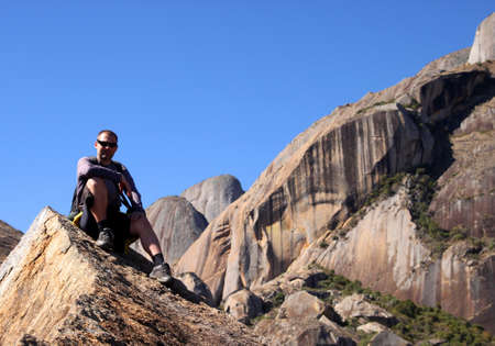 anja: Man sitting on the rocky edge in Anja Reserve in Madagascar