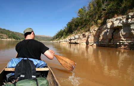 Paddling small canoe on the Tsiribihina river in Madagascar Stock Photo - 8544396