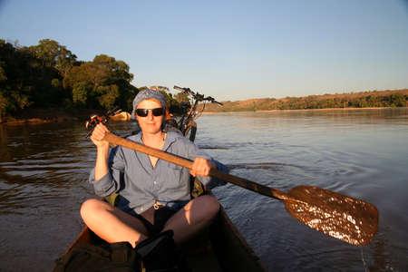 Paddling small canoe on the Tsiribihina river in Madagascar Stock Photo - 8544389