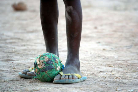 poor people: Home-made football ball at the feet of poor african boy