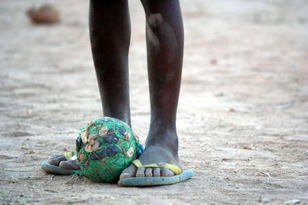 gente pobre: Pelota de f�tbol hechos en casa a los pies de pobre ni�o africano Foto de archivo