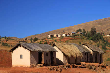 Row of four primitive huts in central plateau in Madagascar Imagens
