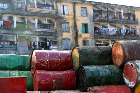 Barrels with waste left in front of a block of flats, Tamatave, Madagascar photo