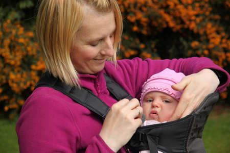 Mother carrying Her daughter In a baby carrier Stock Photo - 13524871