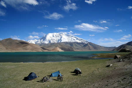 Cyclists camp at the stunning Kara Kul lake, China photo