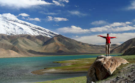 Woman standing on top of a huge rock on the shore of Kara Kul lake in Karakorum mountains, Xinjang province in China photo