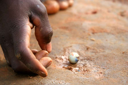 Small Malagasy boy playing with tiny balls Stock Photo