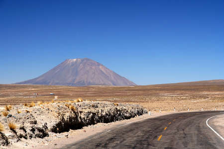 Road through high mountain plateau with the high volcaone in the background, Peru photo