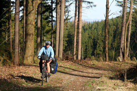 oamaru: Woman cycling through the forest in spring Stock Photo