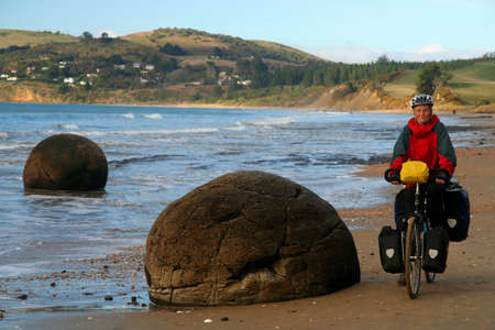 oamaru: Woman on a cycle touring trip in New Zealand, on the beach with Moeraki boulders