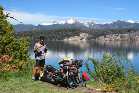 Male cyclist taking a break during touring trip in Lake District, Argentina photo