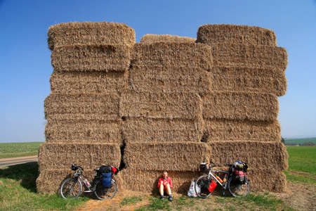 Woman cyclist taking a break next to the high haystack In the field In Czech Republic Stock Photo - 14935641