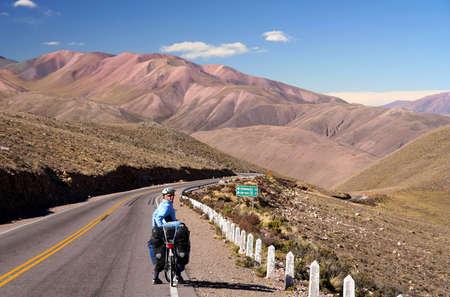 bonne aventure: Vélo femme sur la route vide dans la partie reculée du nord ouest de l'Argentine