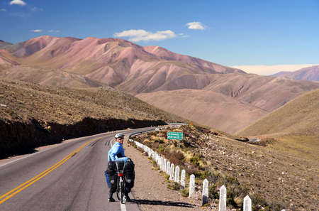 tours: Woman cycling on the empty road in the remote part of north west Argentina
