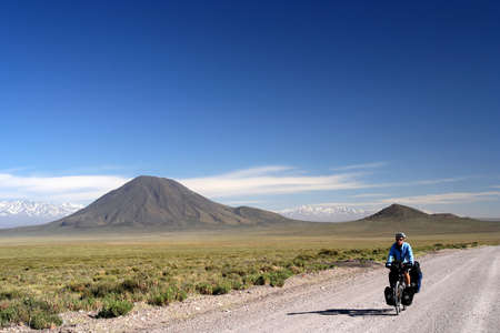 Woman cycling on the famous national Ruta 40 ( quarenta ) in the remote part of central Argentina photo