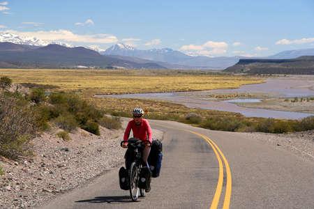 Vrouw fietsen op de beroemde nationale Ruta 40 (quarenta) in het afgelegen deel van het centrum van Argentinië
