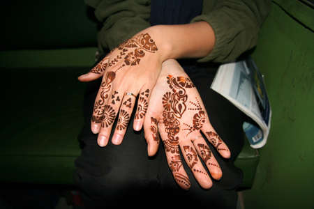 Tourist showing her hands painted in henna photo