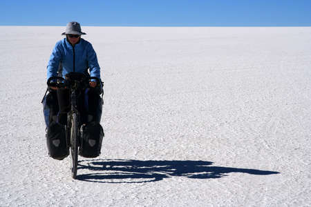 Lonely female cyclist travelling through the biggest salar in the world � Salar de Uyuni in Bolivia photo